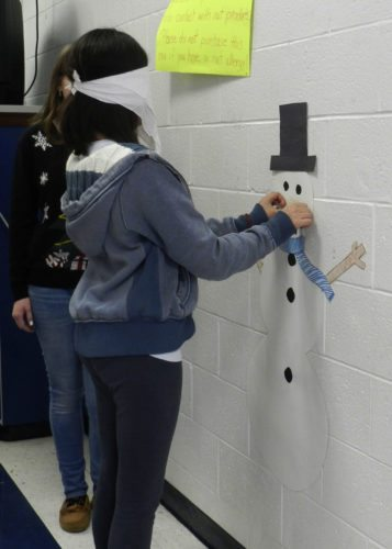 Cydmarie Santiago, 17, of Woodstock, plays Pin the Nose on the Snowman during a Christmas Party at Central High School on Tuesday.  Kaley Toy/Daily